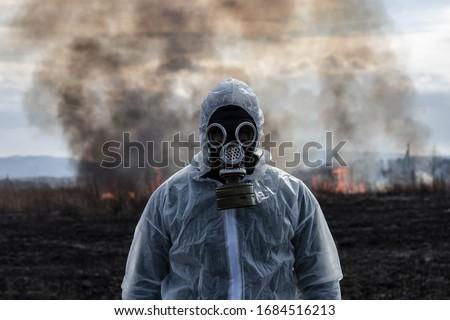 A man in a gas mask in a chemical protective suit shrouded in smoke is walking in a dangerous radioactive zone. A Stalker soldier. Post-Apocalypse. Nuclear war. Environmental disaster. #1684516213