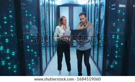 Couple of server engineers cooperating in high tech data center. Male and female technicians updating hardware inspecting system performance in server room. Royalty-Free Stock Photo #1684519060