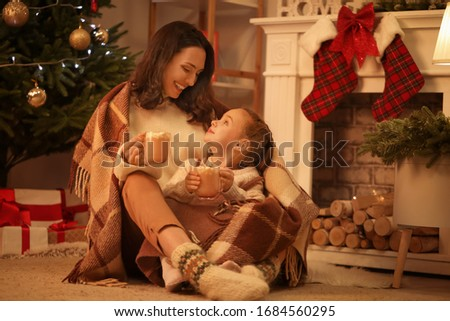 Woman and her little daughter drinking tasty cocoa at home on Christmas eve #1684560295