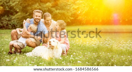 Happy family with children and dog together in the garden in summer Royalty-Free Stock Photo #1684586566