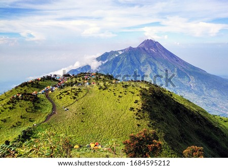 A very beautiful view of Mount Merapi, from one of the hills in Mount Merbabu, there is also a campsite for climbers with colorful tents. #1684595212
