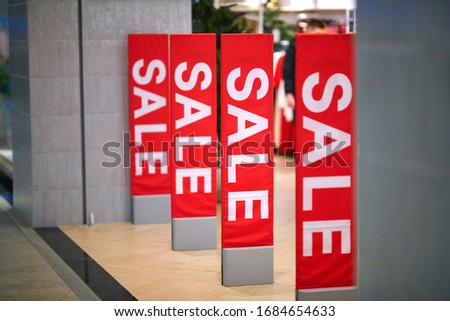 Sale sign at the entrance to clothing store - large red panels with white words. Seasonal discount offer in store. Discounts and black friday concept