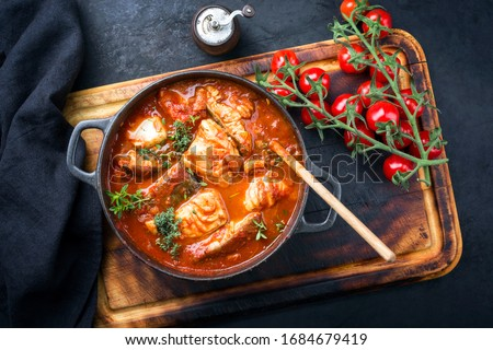 Traditional Brazilian fish stew moqueca baiana with fish filet in tomato sauce as top view in a modern design cast-iron roasting dish  #1684679419