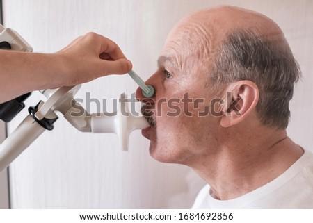 Senior hispanic man man testing breathing function by spirometry. Diagnosis of respiratory function in pulmonary disease Royalty-Free Stock Photo #1684692856