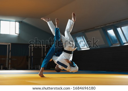 Two young judo caucasian fighters in white and blue kimono with black belts training martial arts in the gym with expression, in action, motion. Practicing fighting skills. Overcoming, reaching target Royalty-Free Stock Photo #1684696180