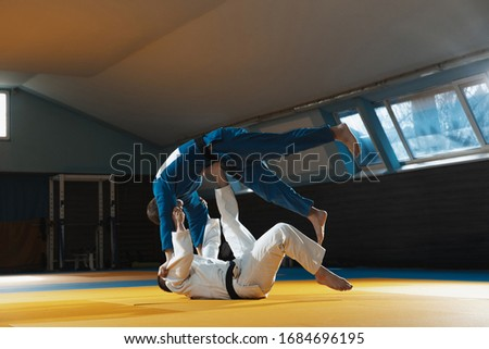 Two young judo caucasian fighters in white and blue kimono with black belts training martial arts in the gym with expression, in action, motion. Practicing fighting skills. Overcoming, reaching target Royalty-Free Stock Photo #1684696195