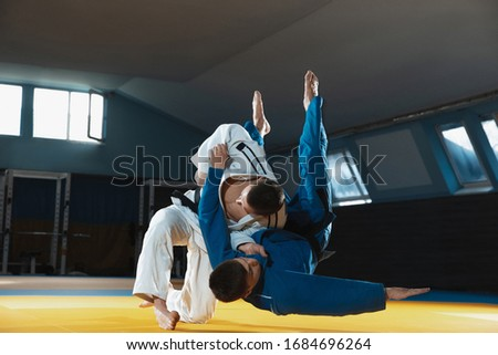 Two young judo caucasian fighters in white and blue kimono with black belts training martial arts in the gym with expression, in action, motion. Practicing fighting skills. Overcoming, reaching target Royalty-Free Stock Photo #1684696264