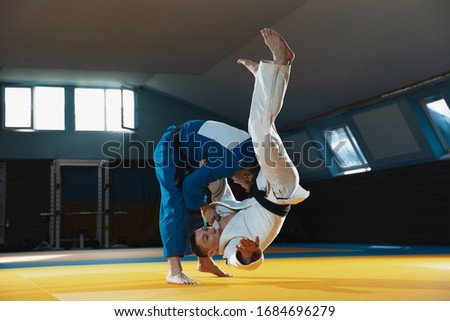 Two young judo caucasian fighters in white and blue kimono with black belts training martial arts in the gym with expression, in action, motion. Practicing fighting skills. Overcoming, reaching target Royalty-Free Stock Photo #1684696279