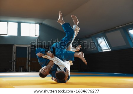 Two young judo caucasian fighters in white and blue kimono with black belts training martial arts in the gym with expression, in action, motion. Practicing fighting skills. Overcoming, reaching target Royalty-Free Stock Photo #1684696297