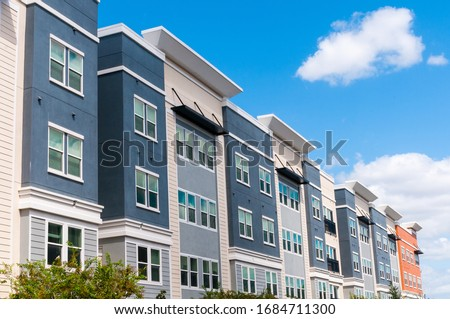Modern luxury urban apartment building exterior with blue sky. Royalty-Free Stock Photo #1684711300