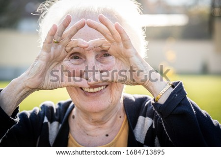 Elderly woman making heart shape with hands