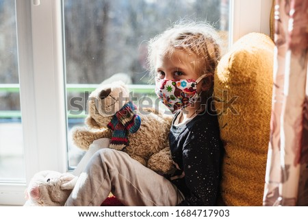 Portrait of a girl in a protective mask . A sick child wearing a protective mask. Patient isolated in house to prevent infection. Coronavirus. Teaching your child preventive measures against covid-19 #1684717903
