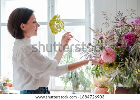 Female professional florist prepares the arrangement of wild flowers. Flower shop. Background concrete gray wall. Concept inspiration, floral, greetings, spring, ornament flowers. #1684726903