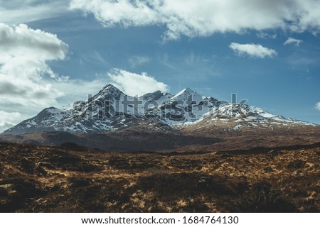 Rugged terrain with snowcapped mountains on the background on the Isle of Skye on the north of Scotland on a sunny spring day Royalty-Free Stock Photo #1684764130