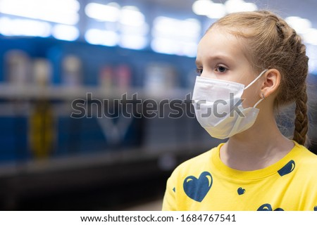 Glad and happy beautiful joy child in the medical helthcare guarding or protecting mask and in yellow t-shirt in the tube, subway or underground hall #1684767541