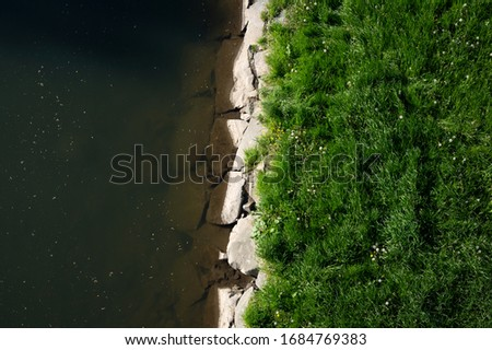 Land with grass and water in the river. Riverbank and shore between two surfaces #1684769383