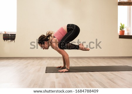 Young sporty woman practising yoga bakasana pose at home #1684788409