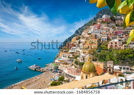 Aerial view of Positano with comfortable beach and blue sea on Amalfi Coast in Campania, Italy. Amalfi coast is popular travel and holyday destination in Europe. Ripe yellow lemons in foreground. Royalty-Free Stock Photo #1684856758