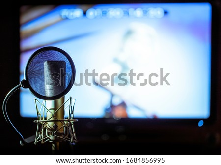 close up of a stereo mic with protector in a dubbing sound studio with the image out of focus in the background screen