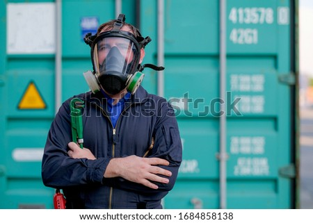 Technician or worker with chemical mask stand and hold wrench in front of green container and look confident. #1684858138