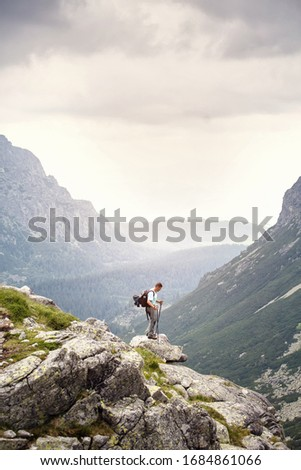 Hiker with backpack standing on top of a mountain. Lifestyle success concept adventure active vacations outdoor happiness freedom emotions. High Tatras mountains. #1684861066