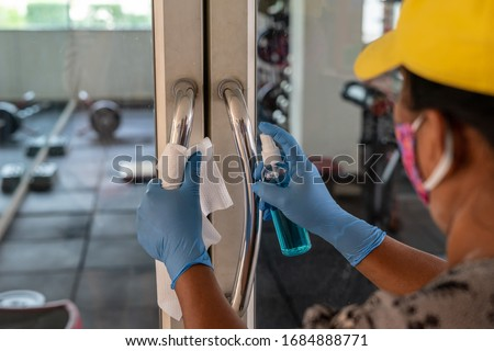 Female Staff using wet wipe and alcohol sanitizer spray to clean the door handle. Antiseptic,disinfection ,cleanliness and heathcare, anti virus concept. Anti Corona virus (COVID-19). Selective focus. #1684888771