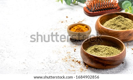 Ayurvedic hair care products. Henna, turmeric and neem powder in bowls on a grey background, copy space. Natural care and hair coloring, free space for text.