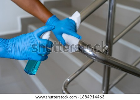 Female hand using wet wipe and alcohol sanitizer spray to clean stainless steel staircase railing.Antiseptic,disinfection ,cleanliness and heathcare, Anti Corona virus (COVID-19). Selective focus. #1684914463