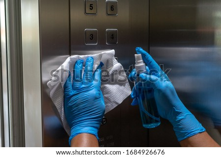 Close up of female hand using wet wipe and alcohol sanitizer spray to clean an elevator push button control panel.Disinfection ,cleanliness and heathcare,Anti Corona virus (COVID-19). Selective focus. #1684926676