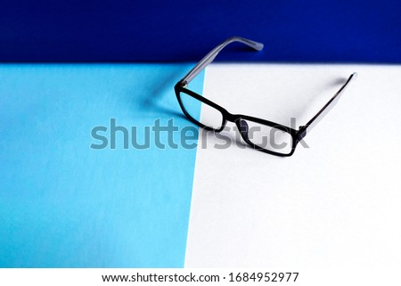 Glasses in a classic black frame on the left side of the tri-color background: blue, navy blue, white. Photo was taken for your perfect design.