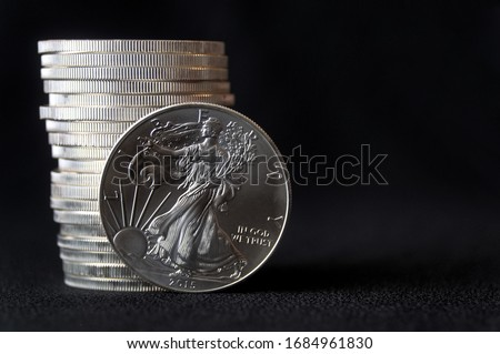 A shiny new American silver eagle coin in front of a stack of similar silver eagle coins #1684961830