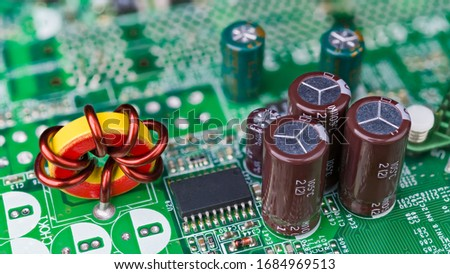 Closeup of toroidal core inductor. Passive electrical components. Electronic induction coil with copper wire winding, microchip, capacitors or resistors soldered on green computer main circuit board. #1684969513