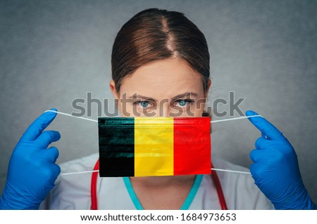 Coronavirus in Belgium Female Doctor Portrait hold protect Face surgical medical mask with Belgium National Flag. Illness, Virus Covid-19 in Belgium, concept photo #1684973653