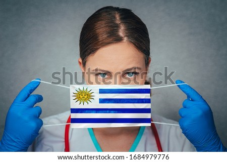 Coronavirus in Uruguay Female Doctor Portrait hold protect Face surgical medical mask with Uruguay National Flag. Illness, Virus Covid-19 in Uruguay, concept photo #1684979776