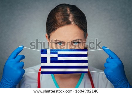 Coronavirus in Greece Female Doctor Portrait hold protect Face surgical medical mask with Greece National Flag. Illness, Virus Covid-19 in Greece, concept photo #1684982140