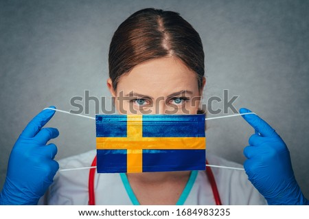 Coronavirus in Sweden Female Doctor Portrait hold protect Face surgical medical mask with Sweden National Flag. Illness, Virus Covid-19 in Sweden, concept photo #1684983235