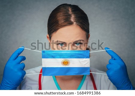 Coronavirus in Argentina Female Doctor Portrait hold protect Face surgical medical mask with Argentina National Flag. Illness, Virus Covid-19 in Argentina, concept photo #1684991386