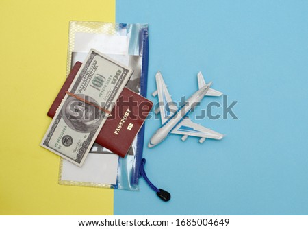 vacation concept. on a yellow-blue background model airplane passport voucher in a plastic transparent bag and dallars. top view #1685004649