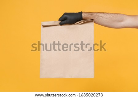 Close up male hold in hand glove brown clear empty blank craft paper bag for takeaway isolated on yellow background. Packaging template mockup. Delivery service concept. Copy space Advertising area #1685020273