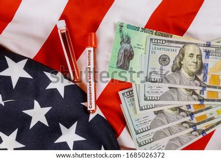 Global pandemic Covid 19 lockdown Coronavirus financial relief package senate stimulus individual checks USA dollar cash banknote on American flag #1685026372