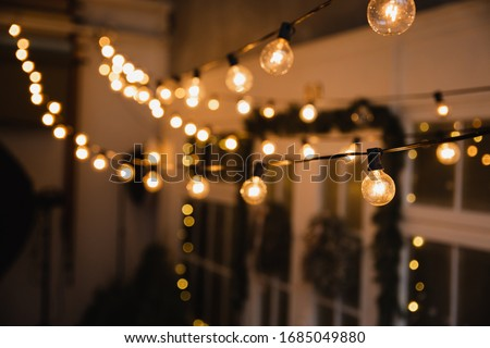 Luminous incandescent lamps hang in the form of a garland on wires, against the background of a shop window. Background from a garland. Incandescent lamps. Royalty-Free Stock Photo #1685049880