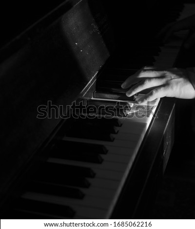 a hand playing an old fashion piano in a blank & white picture