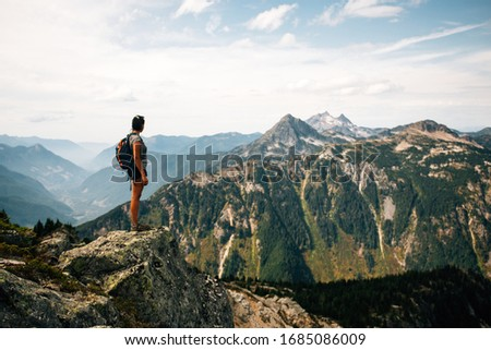People hiking through the British Columbia mountains in the summer time. Lake in the background. Distant mountains. Beautiful scenery.  #1685086009