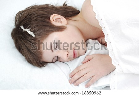 portrait of short haired girl with a tiny feather on her head, laying down on a pillow #16850962