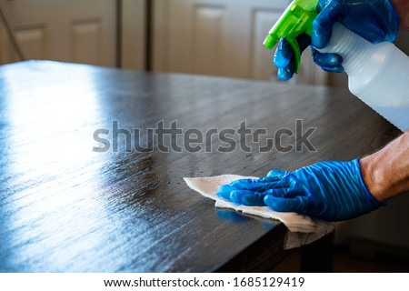 spraying down , wiping , and Cleaning Surfaces with Protective Gloves to disinfect and washing surfaces to protect against the Coronavirus or Covid-19  Royalty-Free Stock Photo #1685129419