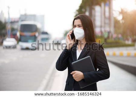 Close up of a businesswoman in a suit wearing Protective face mask and cough, get ready for Coronavirus and pm 2.5 fighting against beside road in background. #1685146324