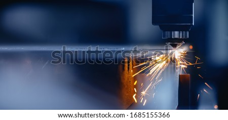 Blue color Laser CNC cut of metal with light spark, technology modern industrial. Royalty-Free Stock Photo #1685155366