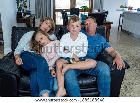 Coronavirus lockdow. Bored family watching tv helpless in isolation at home during quarantine COVID 19 Outbreak. Mandatory lockdowns and self isolation recommendations forces families stay home. #1685188546