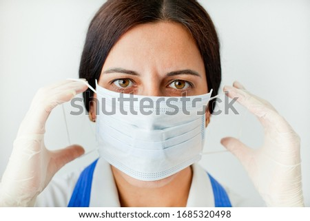 Tired, beautiful female doctor in a protective mask looks at us close-up. Protection against coronavirus Covid-19. #1685320498