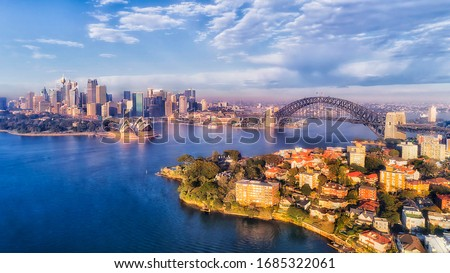 BLue water of Sydney harbour with major city landmarks on waterfront of CBD and north shore in aerial view. #1685322061